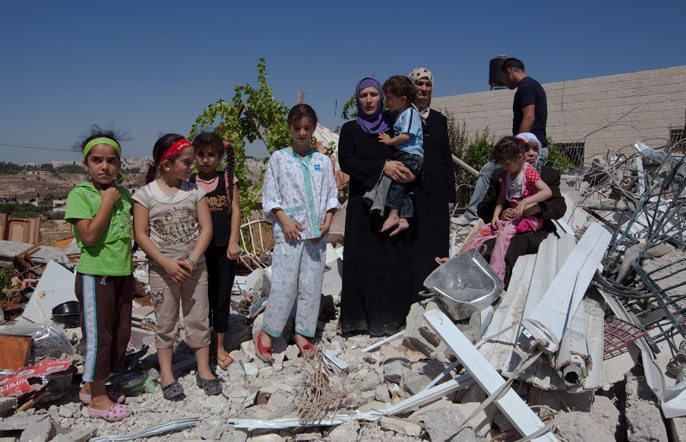 A Palestinian family stands in the remains of their house, that has been demolished by the Israeli authorities in the Beit Hanina neighborhood